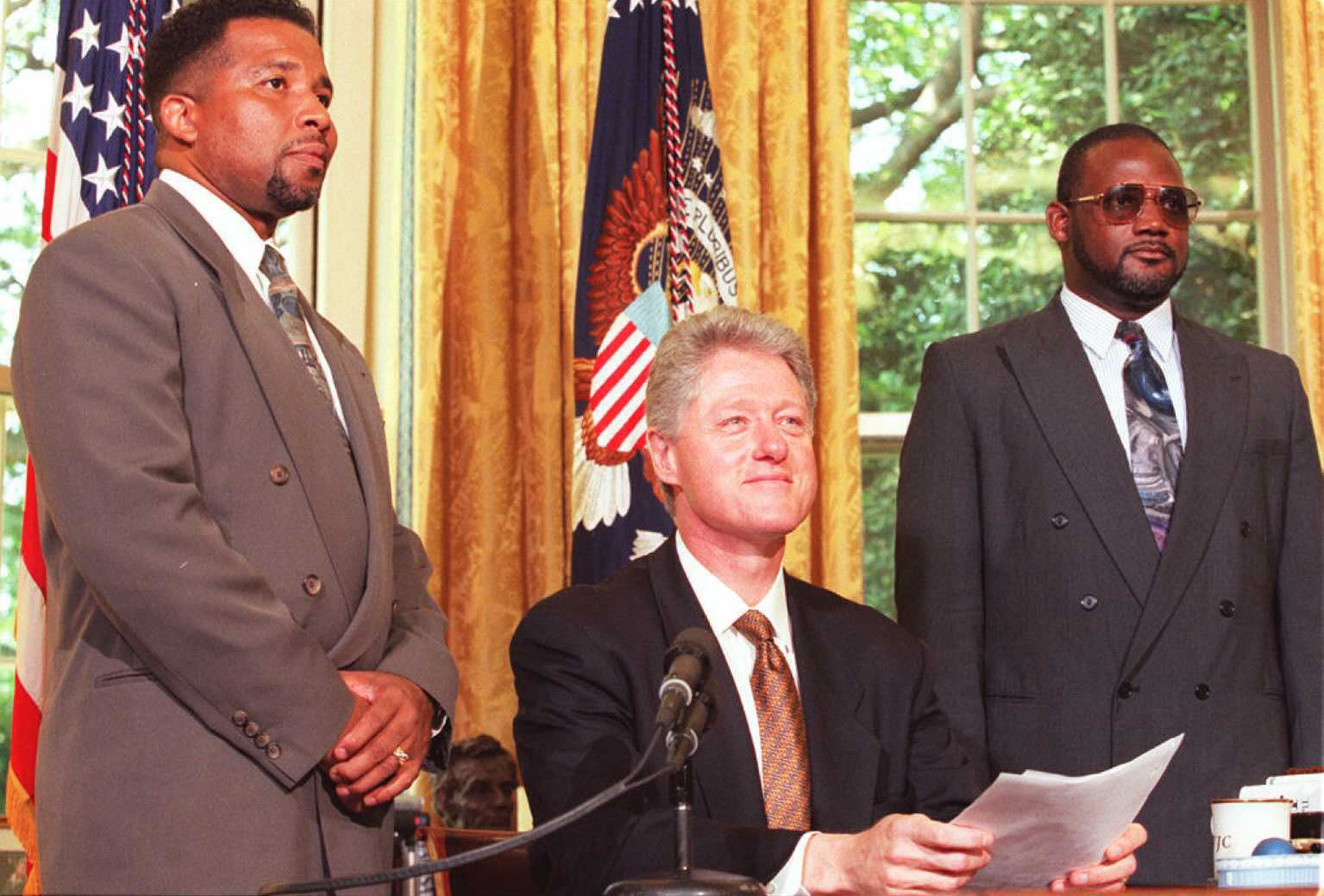 President Bill Clinton( reads his radio address on June 8, 1996 at the White House in Washington, DC. With him are Reverend Terrence Mackey, left, from Greeleyville, SC and Reverend Alvin Anderson, from Tennessee both of whom had their churches attacked by arsonists.  (Getty)