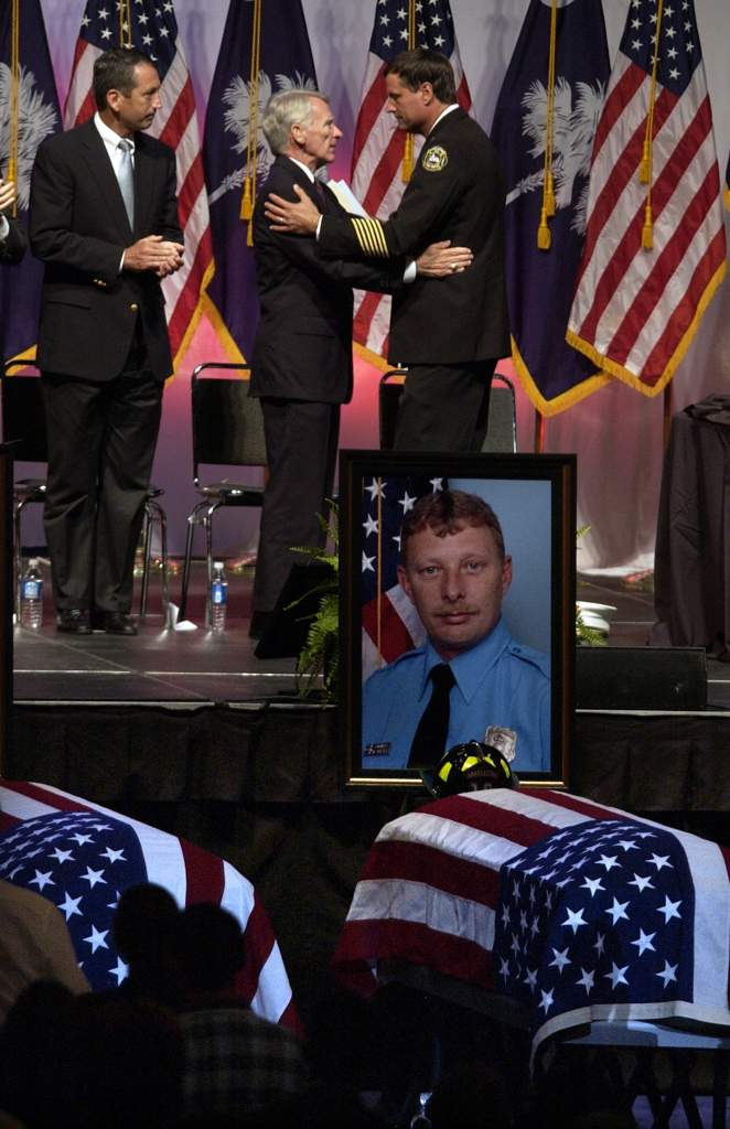 Mayor Joseph P. Riley (C) and Charleston, South Carolina Chief Russell Thomas, Jr. (R) embrace during a memorial service for nine Charleston firefighters at the North Charleston Coliseum June 22, 2007 in North Charleston, South Carolina. The nine where killed when fire swept through a furniture warehouse, collapsing its roof and killing all the firefighters inside.  (Photo by Stephen Morton/Getty Images)