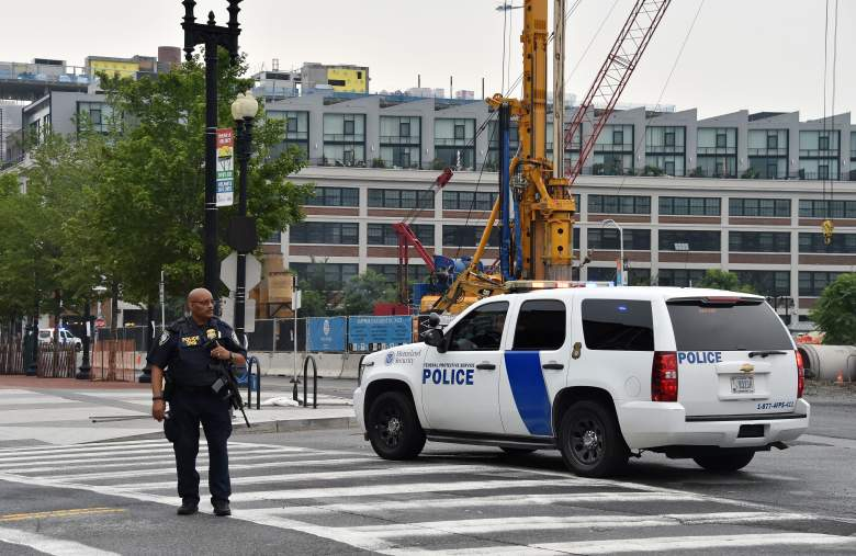 """A police officer patrols near the scene of an unconfirmed shooting at the Navy Yard in Washington, DC on July 2, 2015. The Navy Yard in Washington was put on lockdown Thursday amid unconfirmed reports of an active gunman on the military facility, the scene of a deadly shooting two years ago, the US Navy said. A Navy officer who was inside the complex told CNN people scrambled for cover after hearing someone shout to get out of the building and stay away from the cafeteria.  But Lieutenant Commander Scott Williams said he heard no shots or saw any signs of a struggle. """"We heard someone scream, get out of the building, stay away from the cafeteria and we saw everyone running for the exits or adjoining offices,"""" he said. AFP PHOTO/ MLADEN ANTONOV        (Photo credit should read MLADEN ANTONOV/AFP/Getty Images)"""