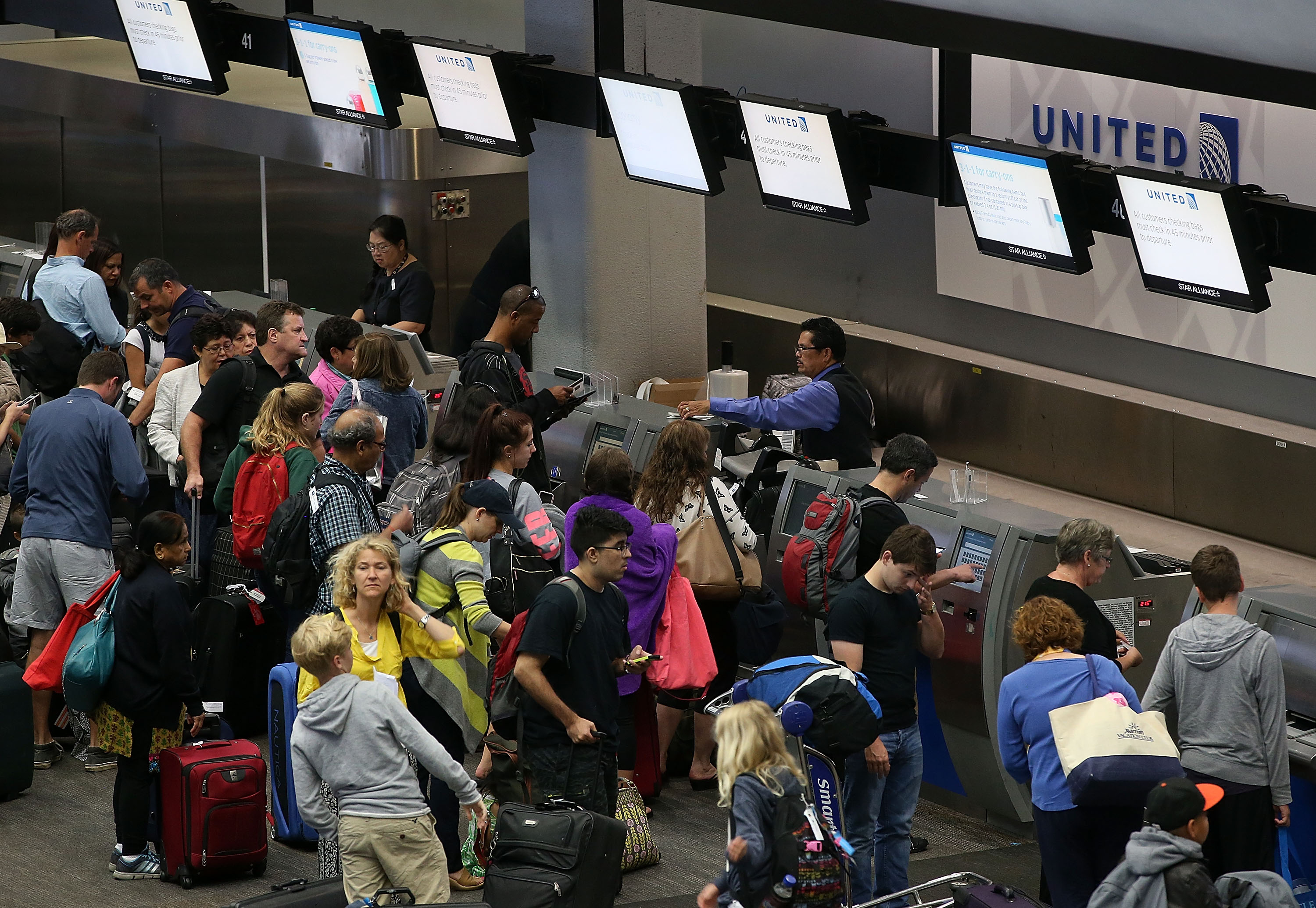 United Airlines passengers wait in line to check in for flights at San Francisco International Airport on Wednesday. (Getty)