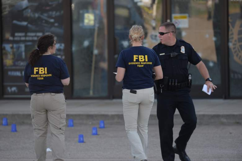 Unidentified members of the FBI Evidence Response Team work with a police officer at the scene of a shooting at a Chattanooga recruitment office.  (Getty Images)
