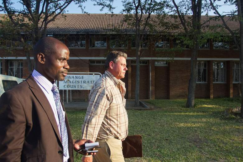 "Professional Zimbabwean hunter Theo Bronkhorst (R) and his defence lawyer Givemore Muvhiringi (L) leave the Magistrate's Court in Hwange on July 29, 2015, after proceedings on poaching charges. Bronkhorst and local landowner Honest Ndlovu appeared in a Zimbabwean court on poaching charges on July 29 after a wealthy American dentist killed a beloved lion just outside a national park, sparking criticism around the world. Cecil the lion, a popular attraction among international visitors to Hwange National Park, was lured beyond the reserve's boundaries by bait and killed earlier this month. Bronkhorst was granted bail on July 29 on charges of ""failing to prevent an illegal hunt"" after he organised the expedition in which the lion was killed by an American dentist and experienced trophy hunter identified as Walter Palmer, who allegedly paid 50,000 USD for the hunt. AFP PHOTO / ZINYANGE AUNTONY        (Photo credit should read Zinyange Auntony/AFP/Getty Images)"