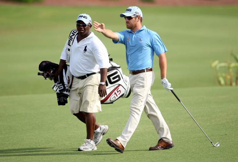 DUBAI, UNITED ARAB EMIRATES - NOVEMBER 20:  Louis Oosthuizen of South Africa walks with his caddie Zack Rasego on the 18th hole during the second round of the Dubai World Championship on the Earth Course, Jumeirah Golf Estates on November 20, 2009 in Dubai, United Arab Emirates.  (Photo by Andrew Redington/Getty Images)