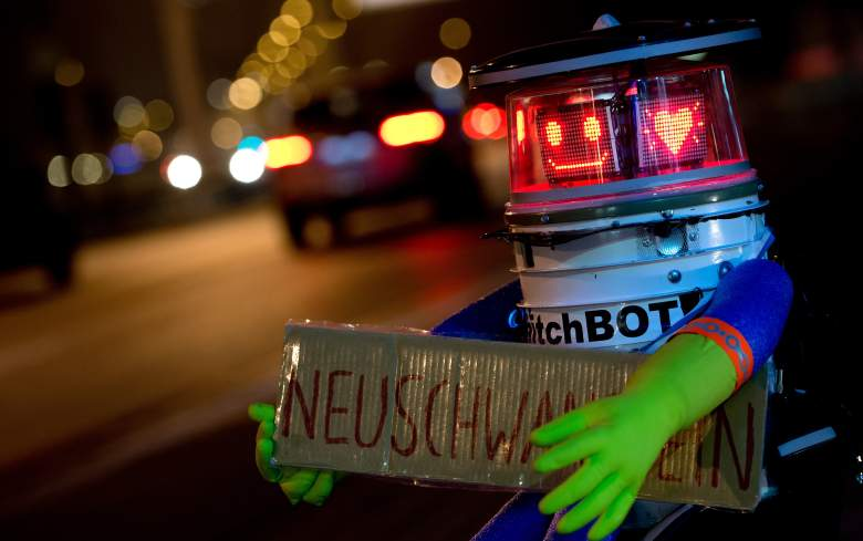 """Robot """"hitchBOT"""" is seen holding a sign reading """"Neuschwanstein"""" as he waits for a lift at the roadside in Munich, southern Germany, on February 13, 2015. HitchBOT, a charming robot assembled using household parts who was hitchhiking more than 6,000 kilometers across Canada in summer 2014 as part of a social experiment, started his tour across Germany, where he is aimed to visit among others Neuschwanstein Castle in the South, the carnival in Cologne (West), the North Sea island of Sylt, the eastern city of Goerlitz near the Polish border and the German capital Berlin.            AFP PHOTO / DPA / SVEN HOPPE   +++   GERMANY OUT        (Photo credit should read SVEN HOPPE/AFP/Getty Images)"""