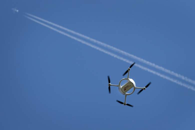 A drone carrying a mail box of Swiss Post flies past on July 7, 2015 above the airport of Bellechasse, western Switzerland during a press conference. Swiss Post started a series of test for parcel delivery by drone in the alpine country that has many isolated villages in valleys surrounded by mountains. AFP PHOTO / FABRICE COFFRINI        (Photo credit should read FABRICE COFFRINI/AFP/Getty Images)