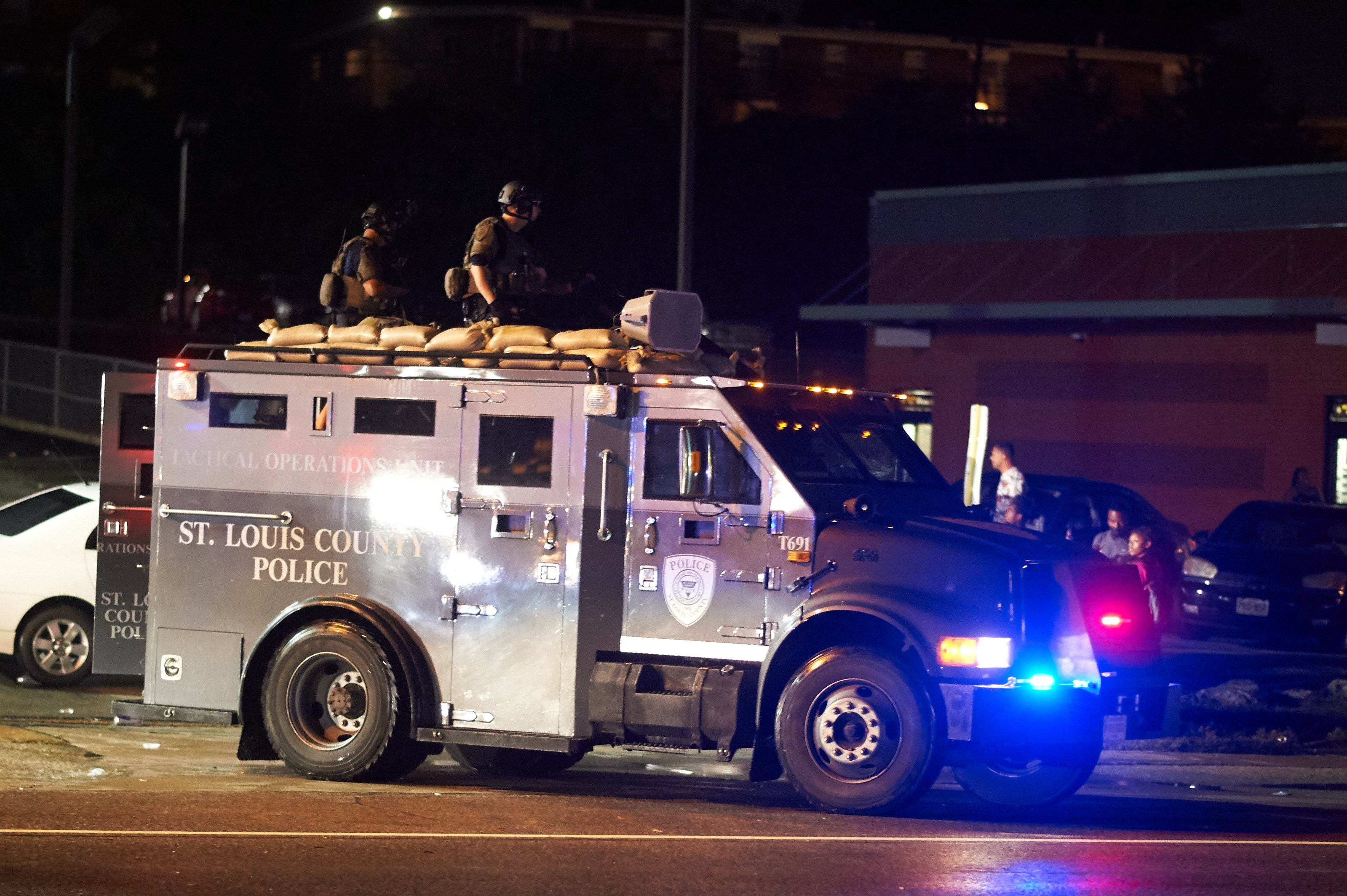 St. Louis County  police officers respond in an MRAP vehicle after shots were fired during a protest march on August 9, 2015 on West Florissant Avenue in Ferguson, Missouri. (Getty)