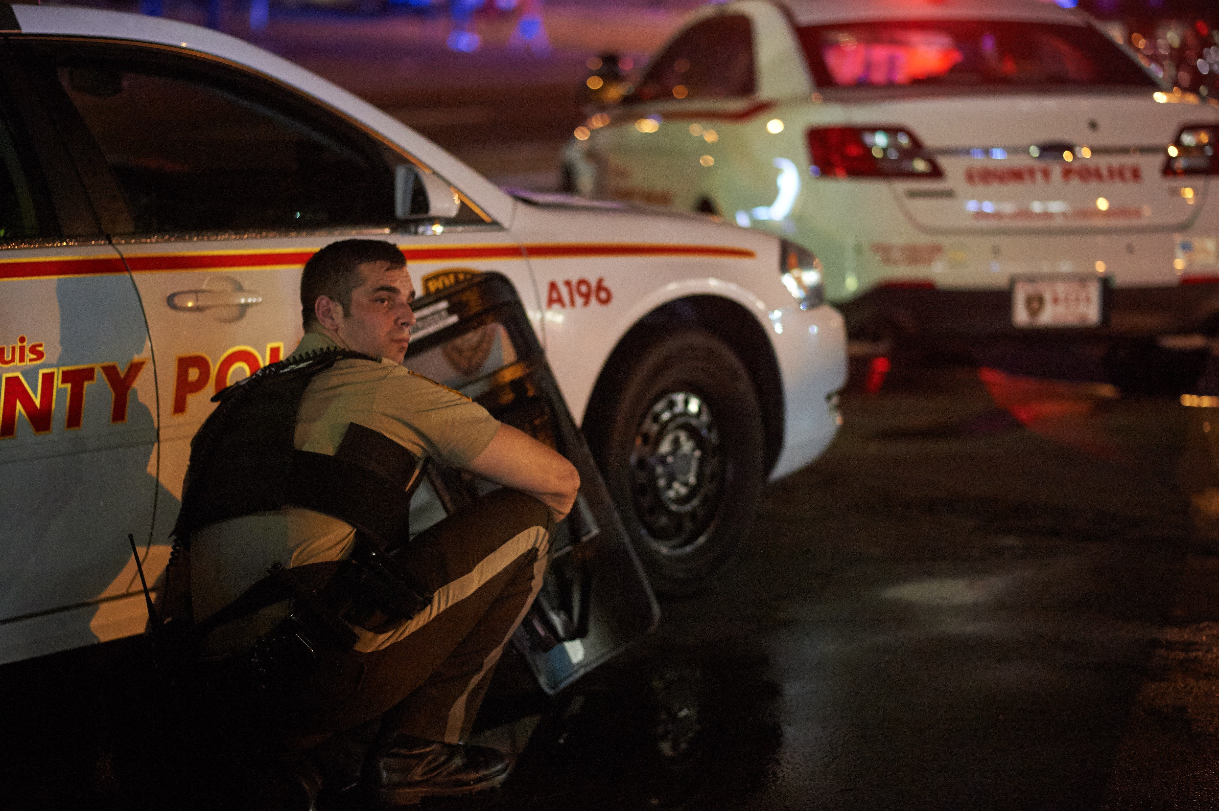 A St. Louis County  police officer takes cover behind a car after shots were fired. (Getty)