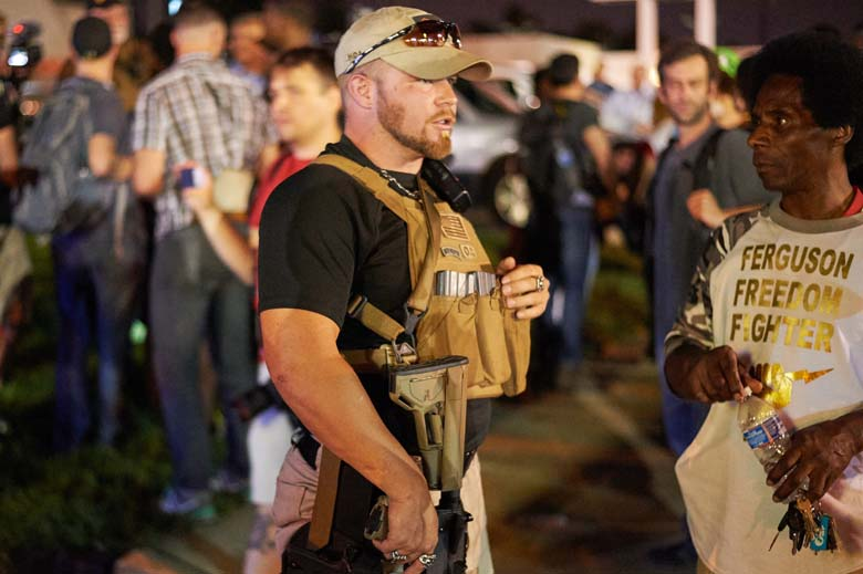 A member of the Oath Keepers walks with his personal weapon on the street during protests in Ferguson, Missouri on August 10, 2015. (Getty)