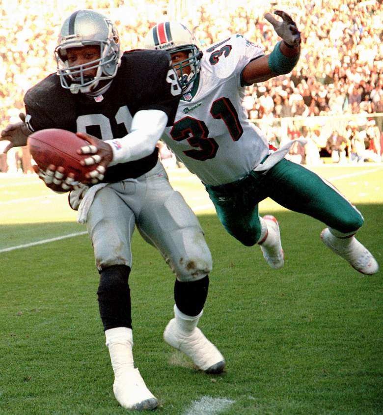 OAKLAND, UNITED STATES:  Miami Dolphin safety Brock Marion (R) moves in for the tackle after Oakland Raider wide-receiver Tim Brown (L) took a pass from quarterback Donald Hollas 06 December in Oakland, California.  AFP PHOTO/John G. MABANGLO (Photo credit should read JOHN G. MABANGLO/AFP/Getty Images)