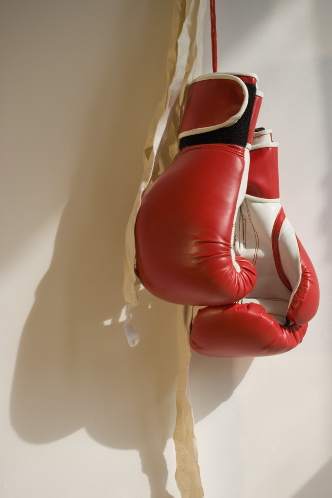 Red Boxing Gloves Hanging on Wall --- Image by © Royalty-Free/Corbis