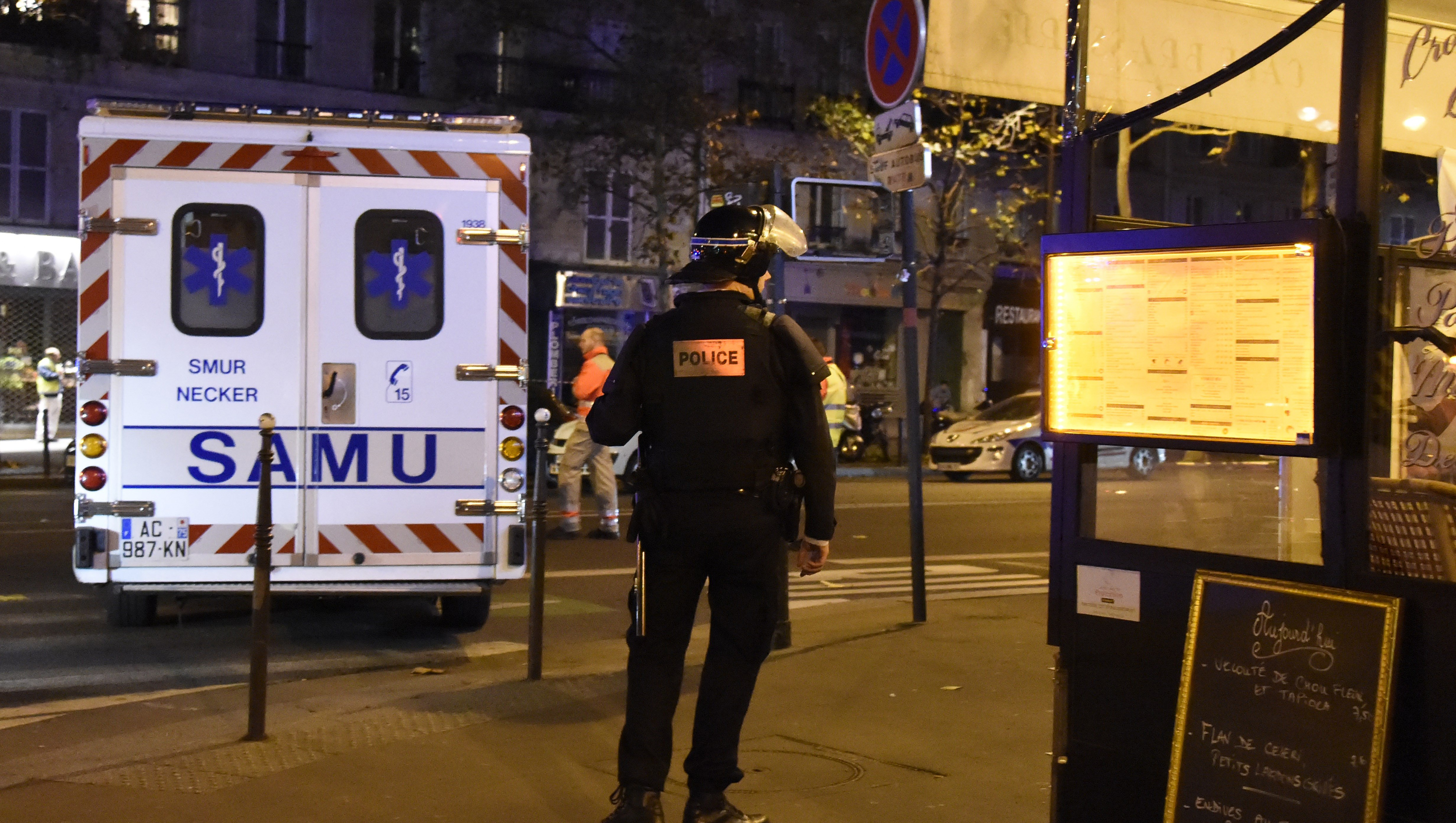 A riot police officer stands by an ambulance near the Bataclan concert hall in central Paris, on November 13, 2015. A number of people were killed and others injured in a series of gun attacks across Paris, as well as explosions outside the national stadium where France was hosting Germany.   AFP PHOTO / DOMINIQUE FAGET        (Photo credit should read DOMINIQUE FAGET/AFP/Getty Images)