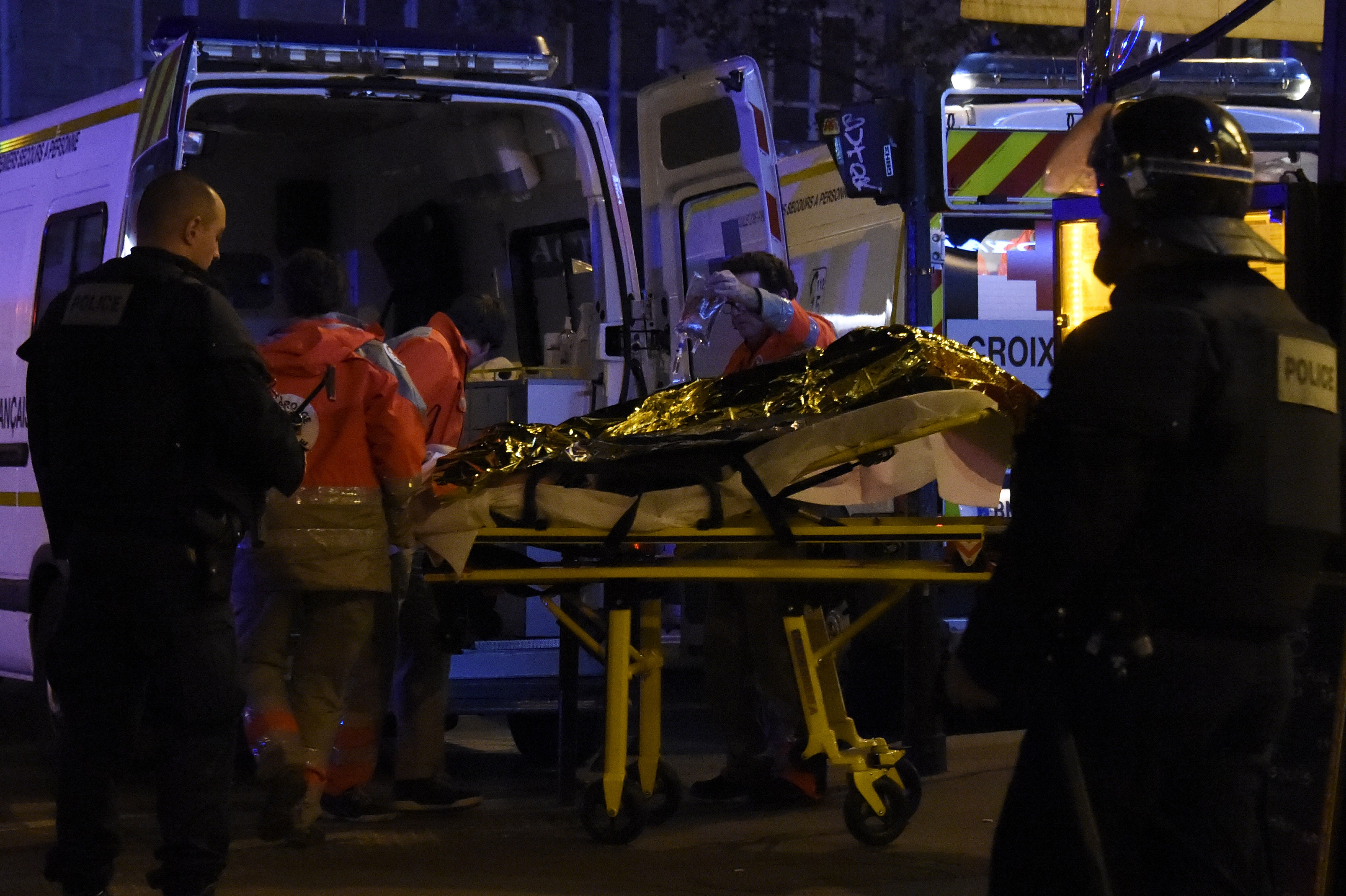 Rescue workers evacuate an injured person near the Bataclan concert hall. (Getty)