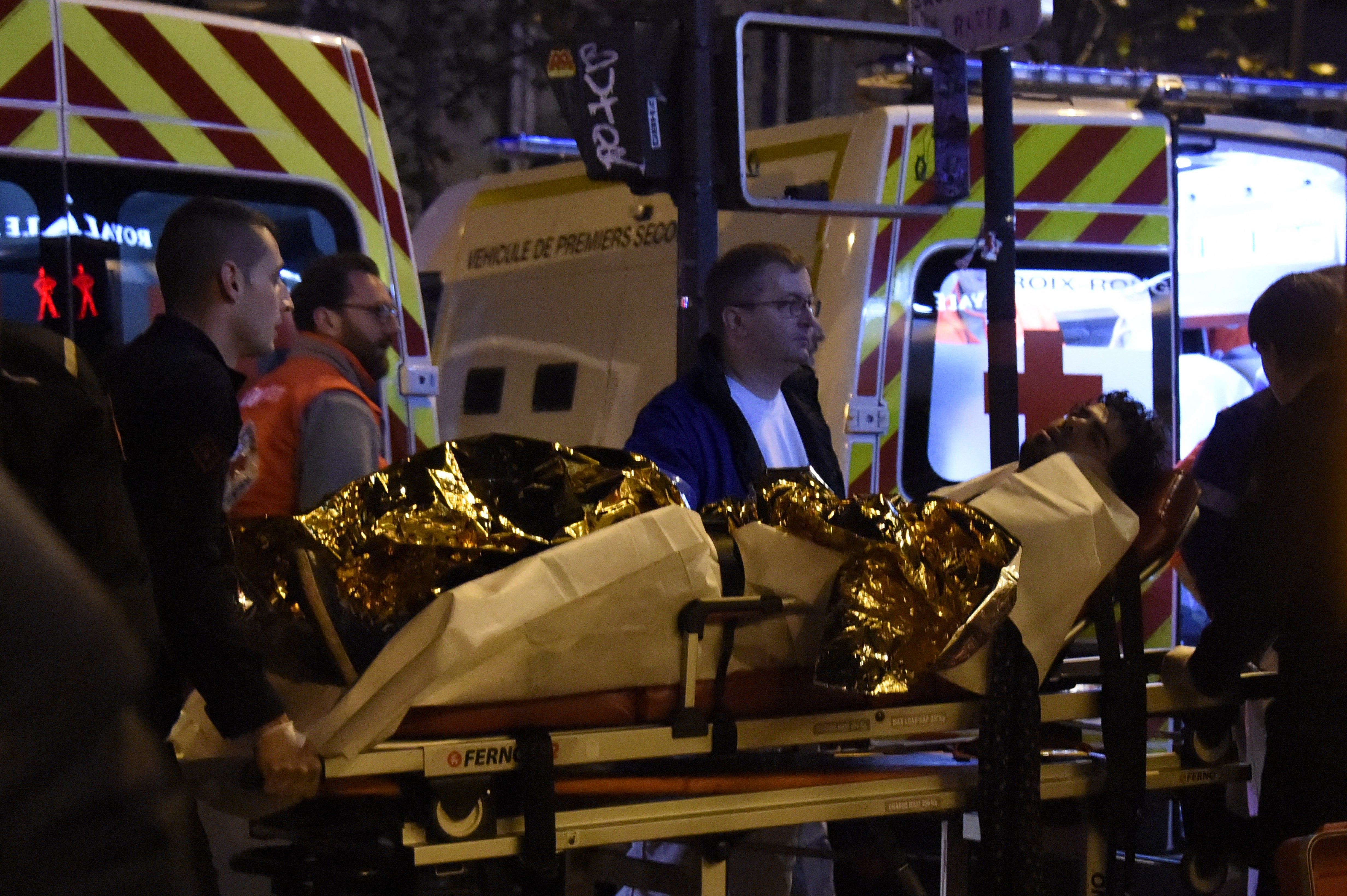 An injured man is evacuated on a stretcher near the Bataclan concert hall. (Getty)