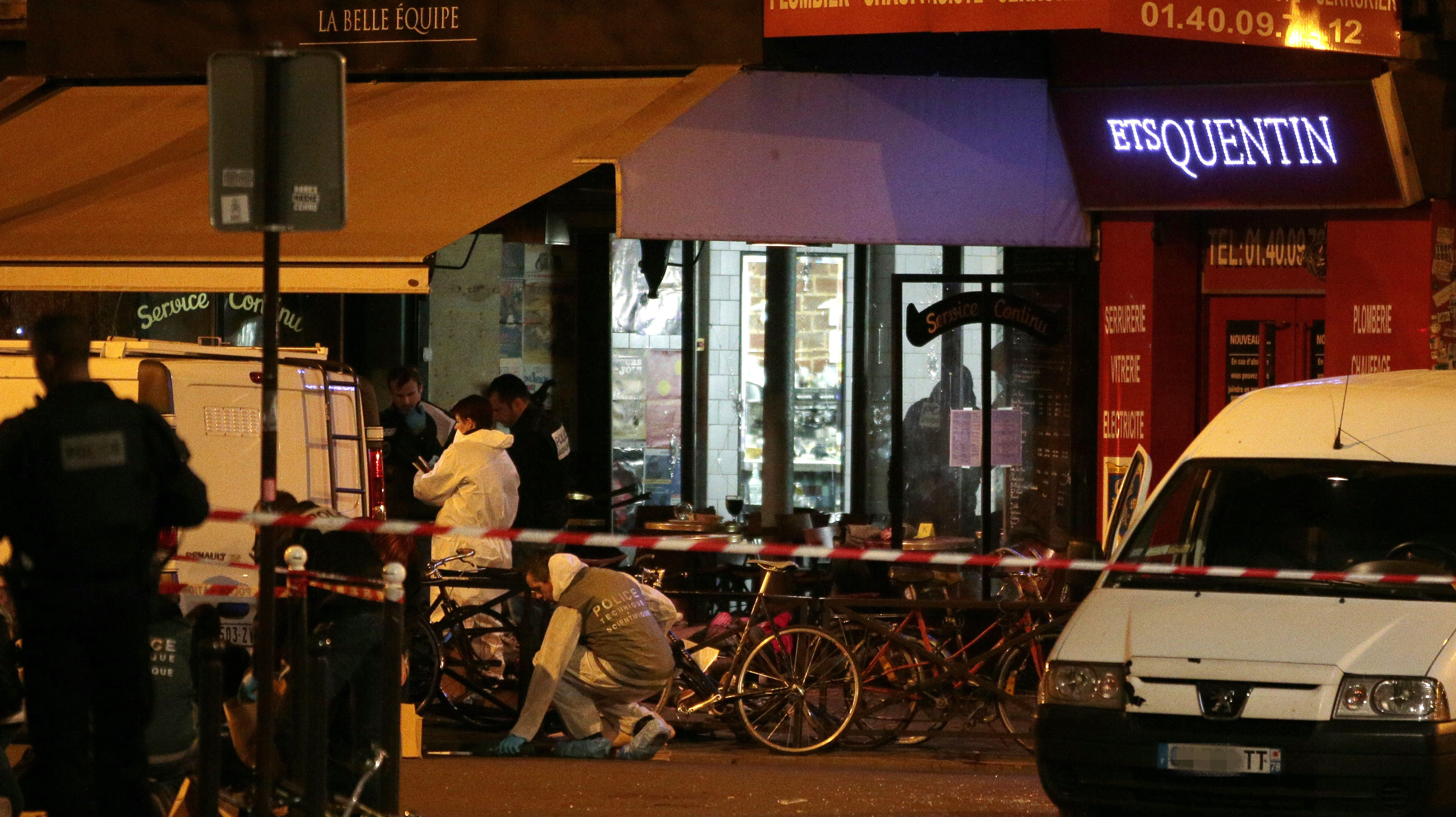 Forensic police search for evidences outside the La Belle Equipe cafe, rue de Charonne, at the site of an attack. (Getty)