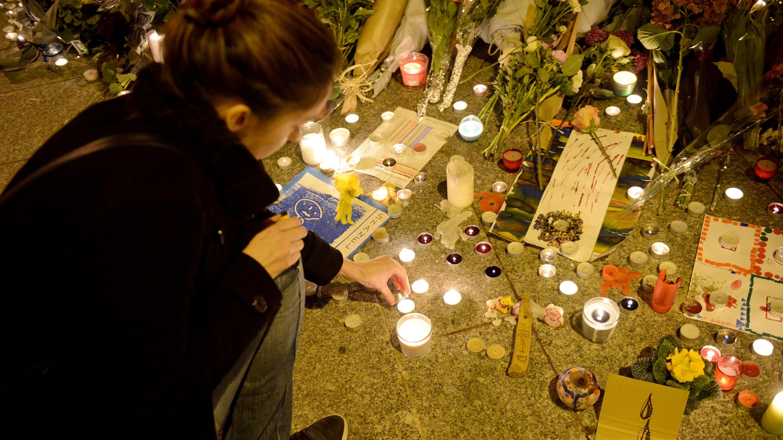 A woman light candles outside Le Carillon bar. (Getty)