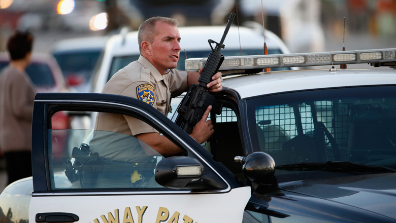 A California Highway Patrol officer stands with his weapon as authorities pursued the suspects. (Getty)