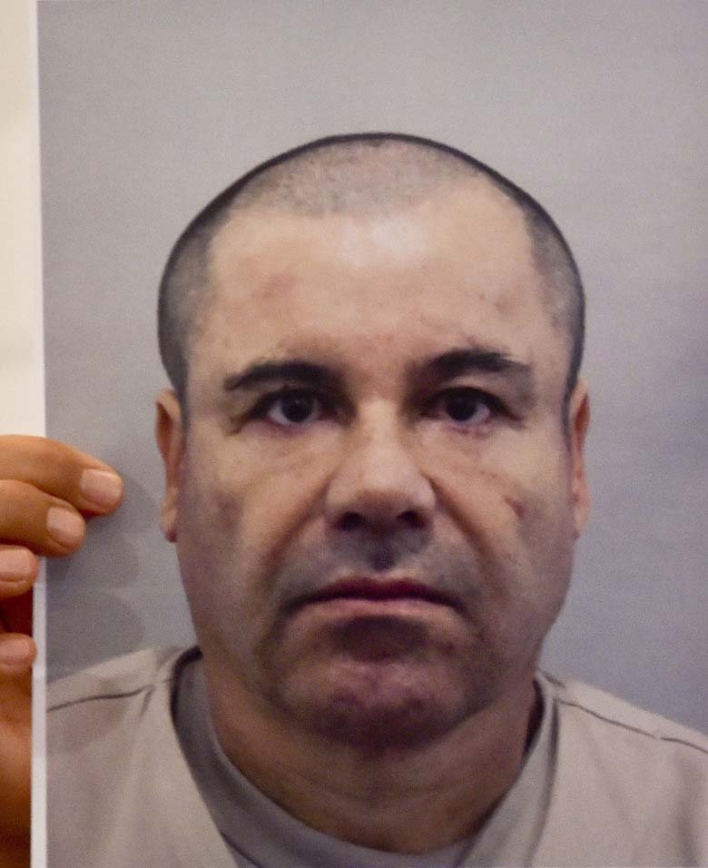 """A man shows a picture of Mexican drug kingpin Joaquin """"El Chapo"""" Guzman during a press conference of Mexico's Attorney General Arely Gomez held at the Interior Ministry building in Mexico City, on July 13, 2015. (YURI CORTEZ/AFP/Getty Images)"""