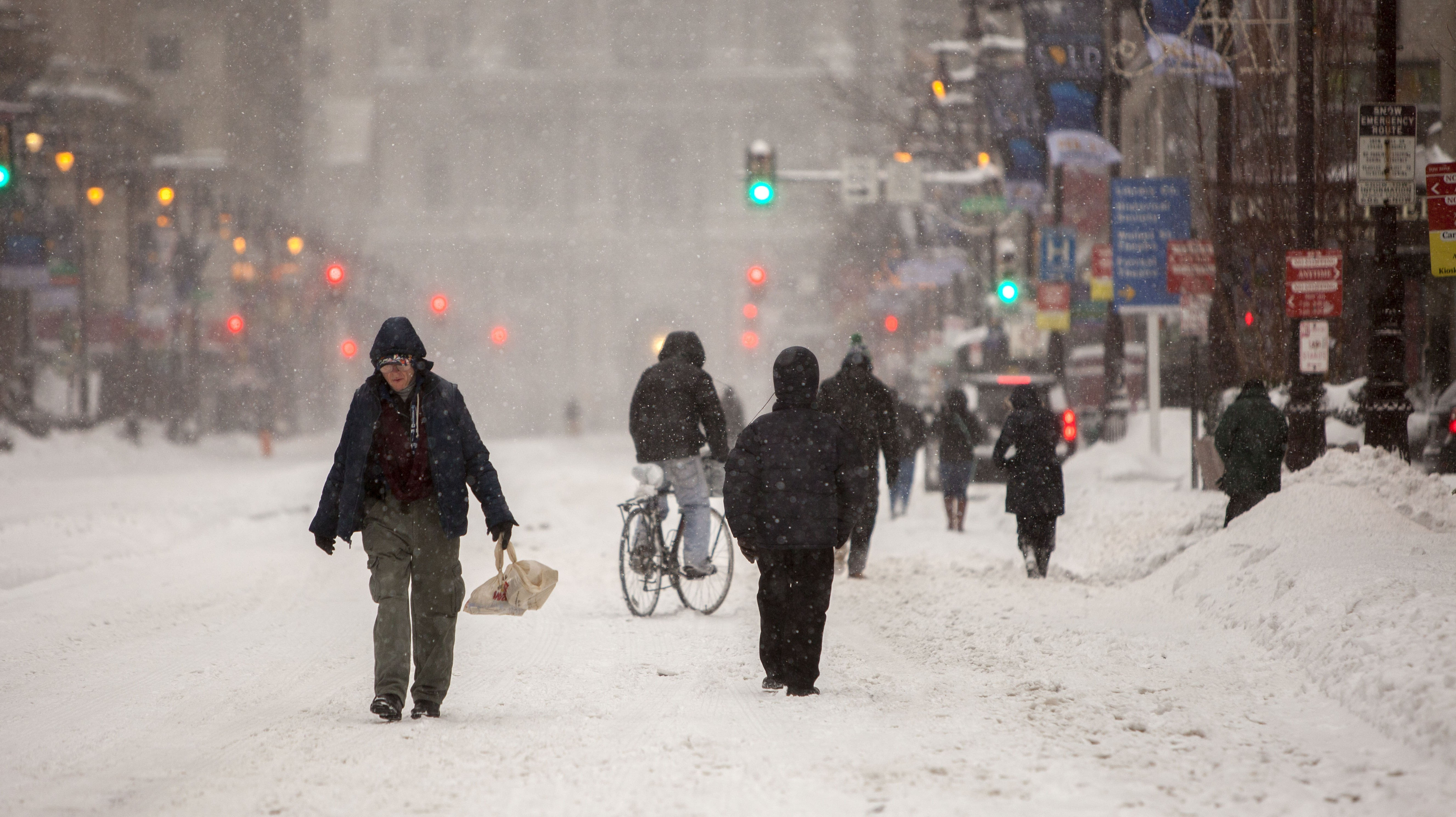 Residents walk along Broad Street in downtown Philadelphia as snow continues to fall on January 23, 2016.  (Getty)