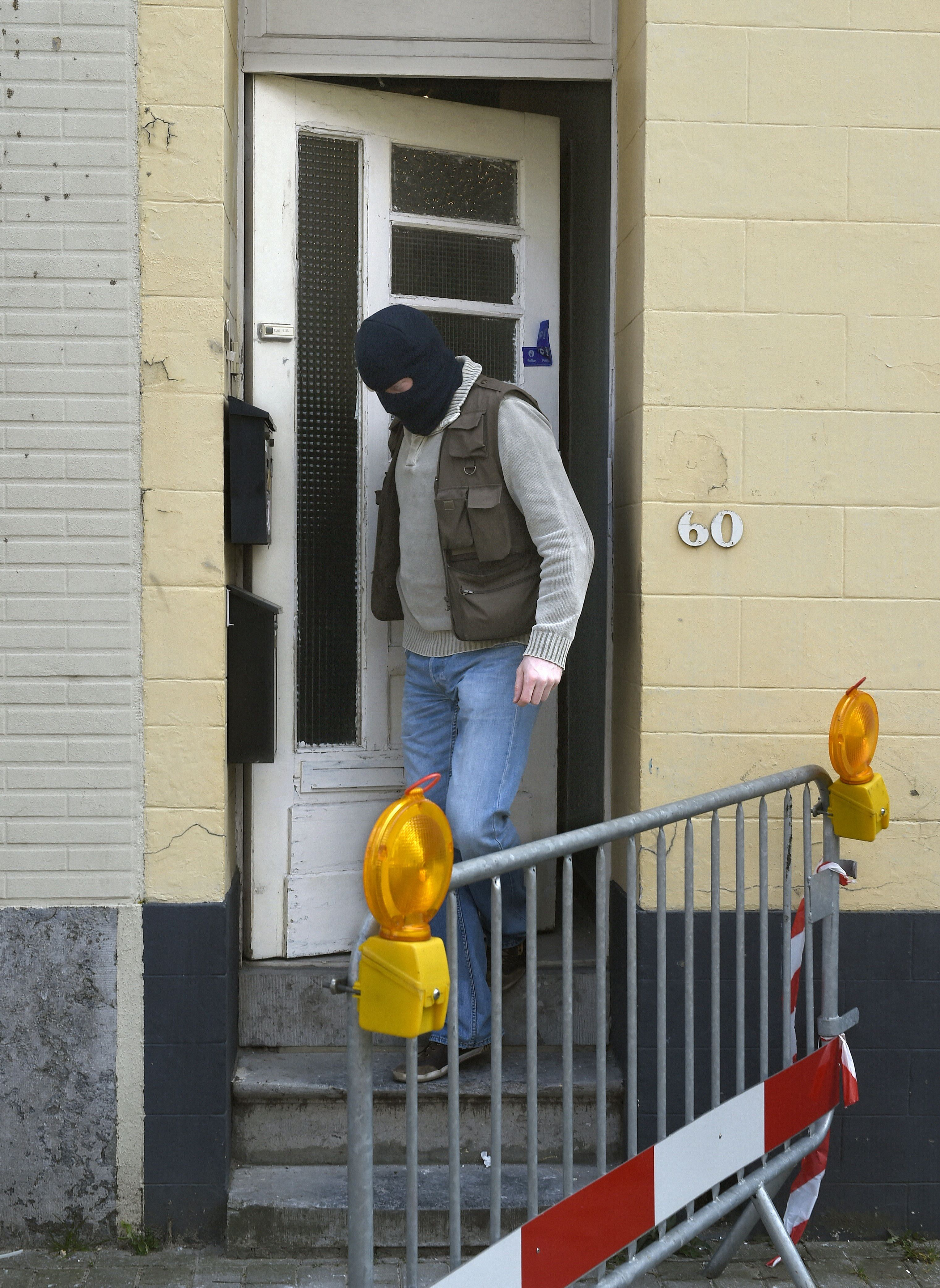 A member of Belgian police leaves on March 16, 2016 the house where a shooting took place the day before during an anti-terror operation in the rue du Dries-Driesstraat in Forest-Vorst, Brussels. (Getty)