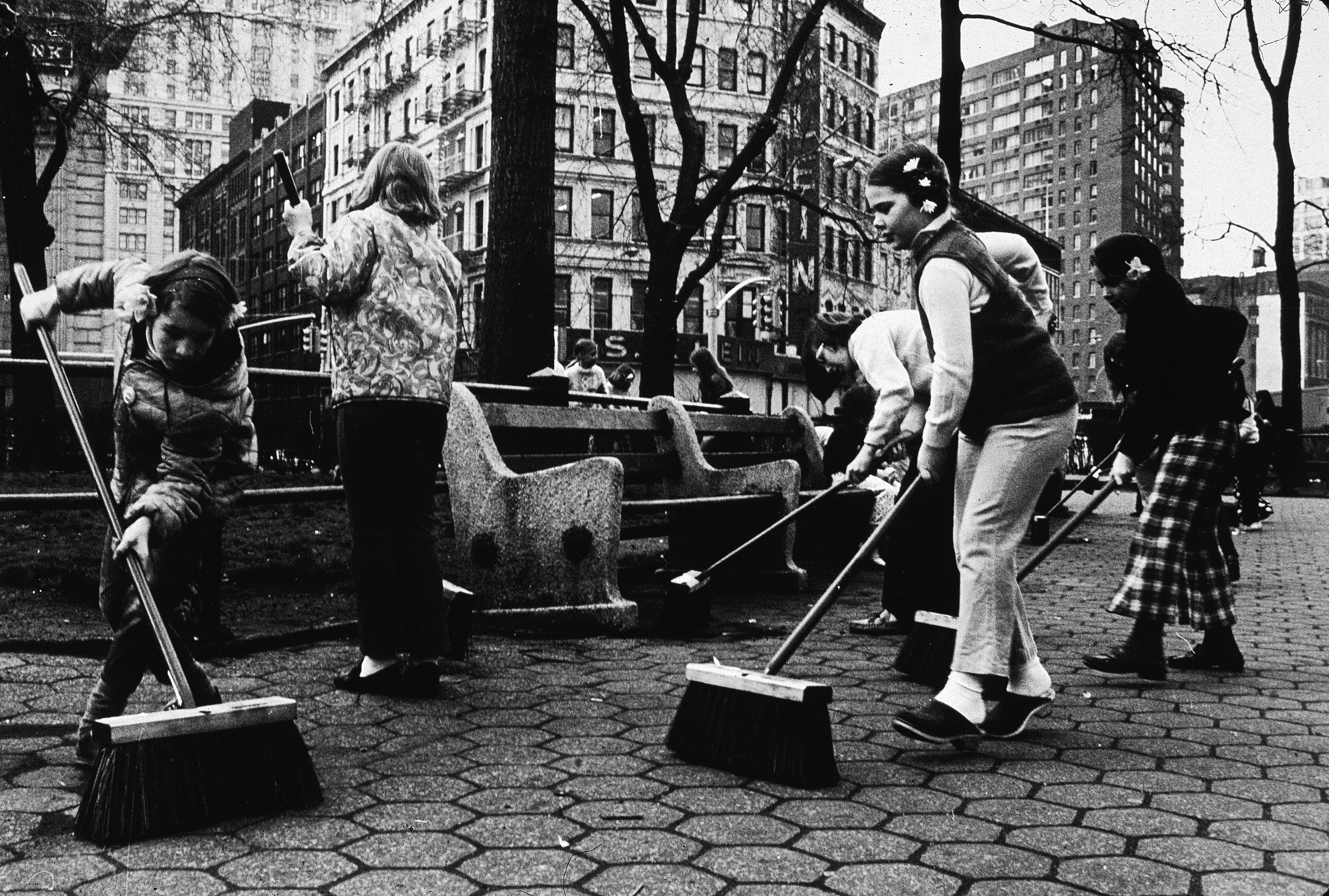 Children use push brooms to sweep a city park during Earth Day, New York City, 1970s. (Photo by Hulton Archive/Getty Images)
