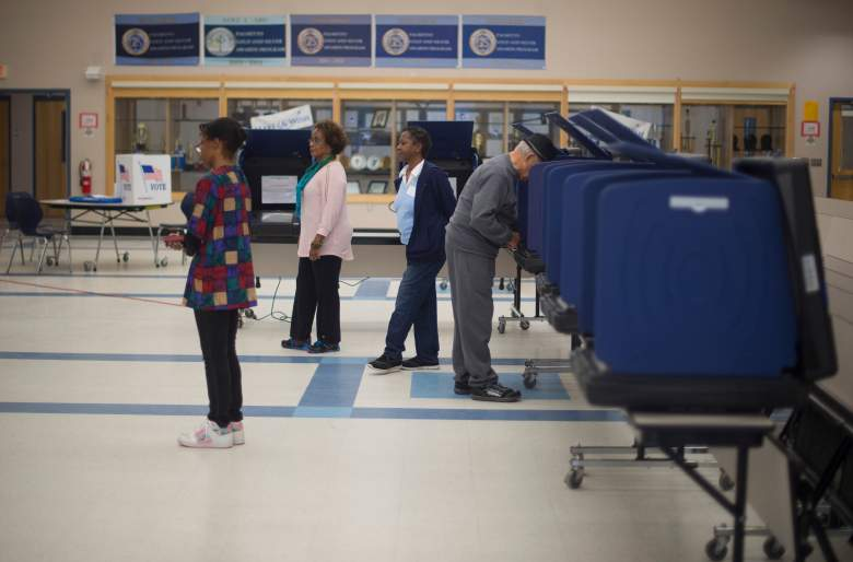 Three polling managers wait for voters as a man casts his ballot in the Republican presidential primaries at Moultrie Middle School in Mount Pleasant, South Carolina, on February 20, 2016. / AFP / JIM WATSON (Photo credit should read JIM WATSON/AFP/Getty Images)