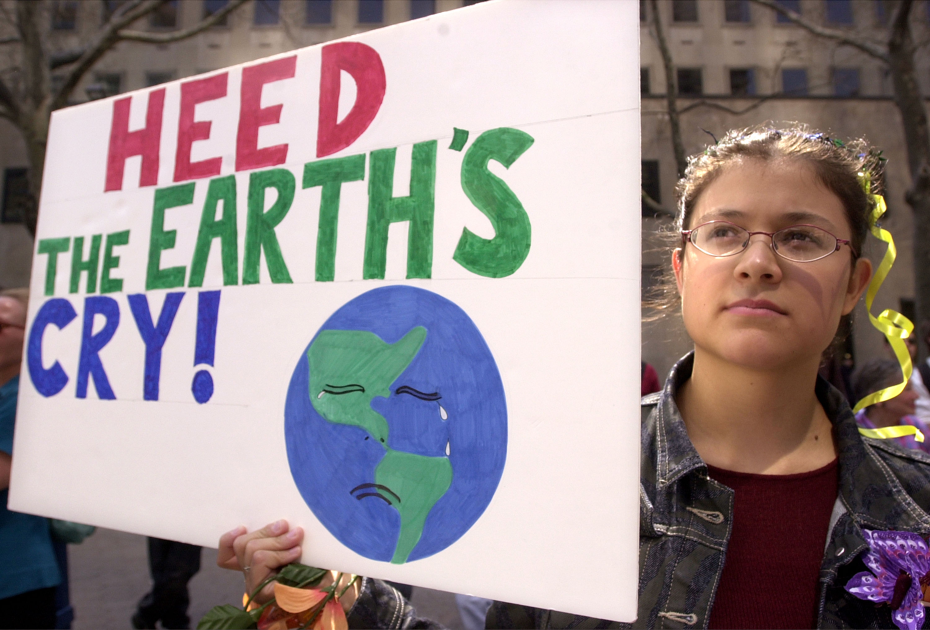 A protester holds a sign at an Earth Day rally April 22, 2001 in front of the United Nations in New York City. (Photo by Spencer Platt/Newsmakers)