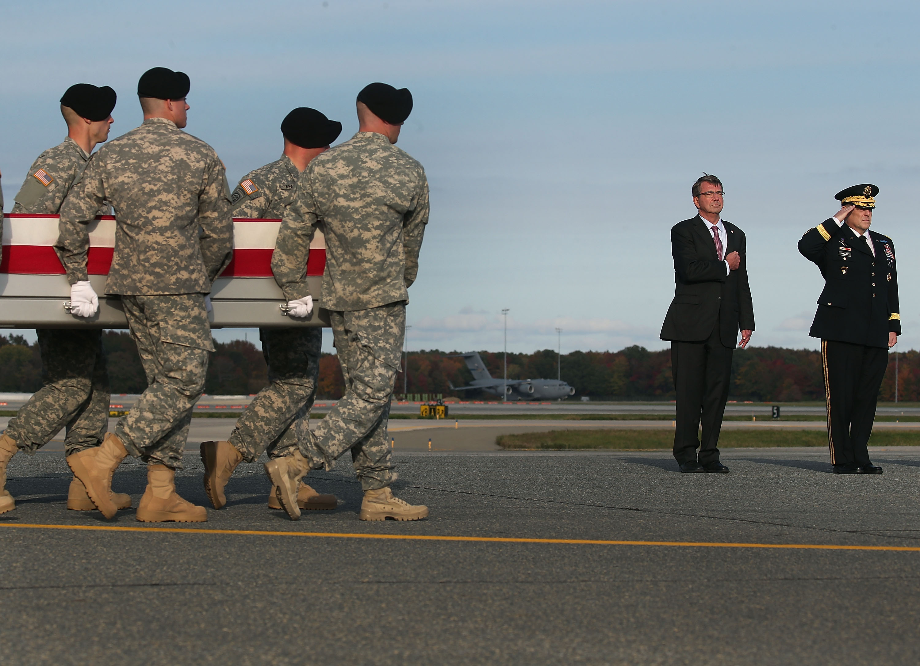 US Secretary of Defense Ash Carter stands at attention with US Army Chief of Staff Gen. Mark Milley while a U.S. Army carry team moves the transfer case of U.S. Army Master Sgt. Joshua L. Wheeler during a dignified transfer at Dover Air Force Base on October 24, 2015 in Dover, Delaware. (Mark Wilson/Getty)
