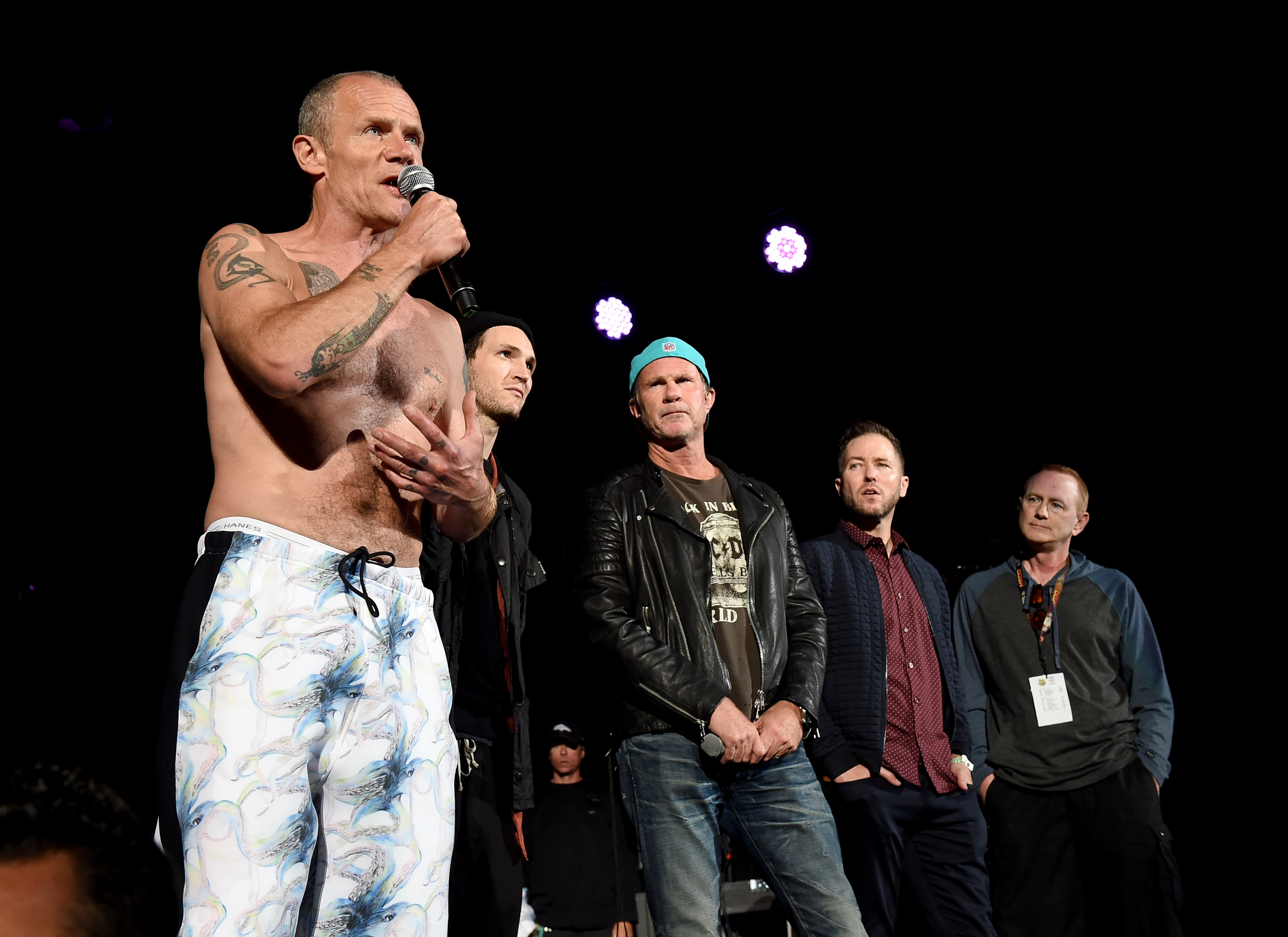 Flea, Josh Klinghoffer, and Chad Smith of music group Red Hot Chili Peppers speak as radio personalities Ted Stryker and Kevin Ryder listen onstage at KROQ Weenie Roast 2016 at Irvine Meadows Amphitheatre on May 14, 2016 in Irvine, California.  (Kevin Winter/Getty)