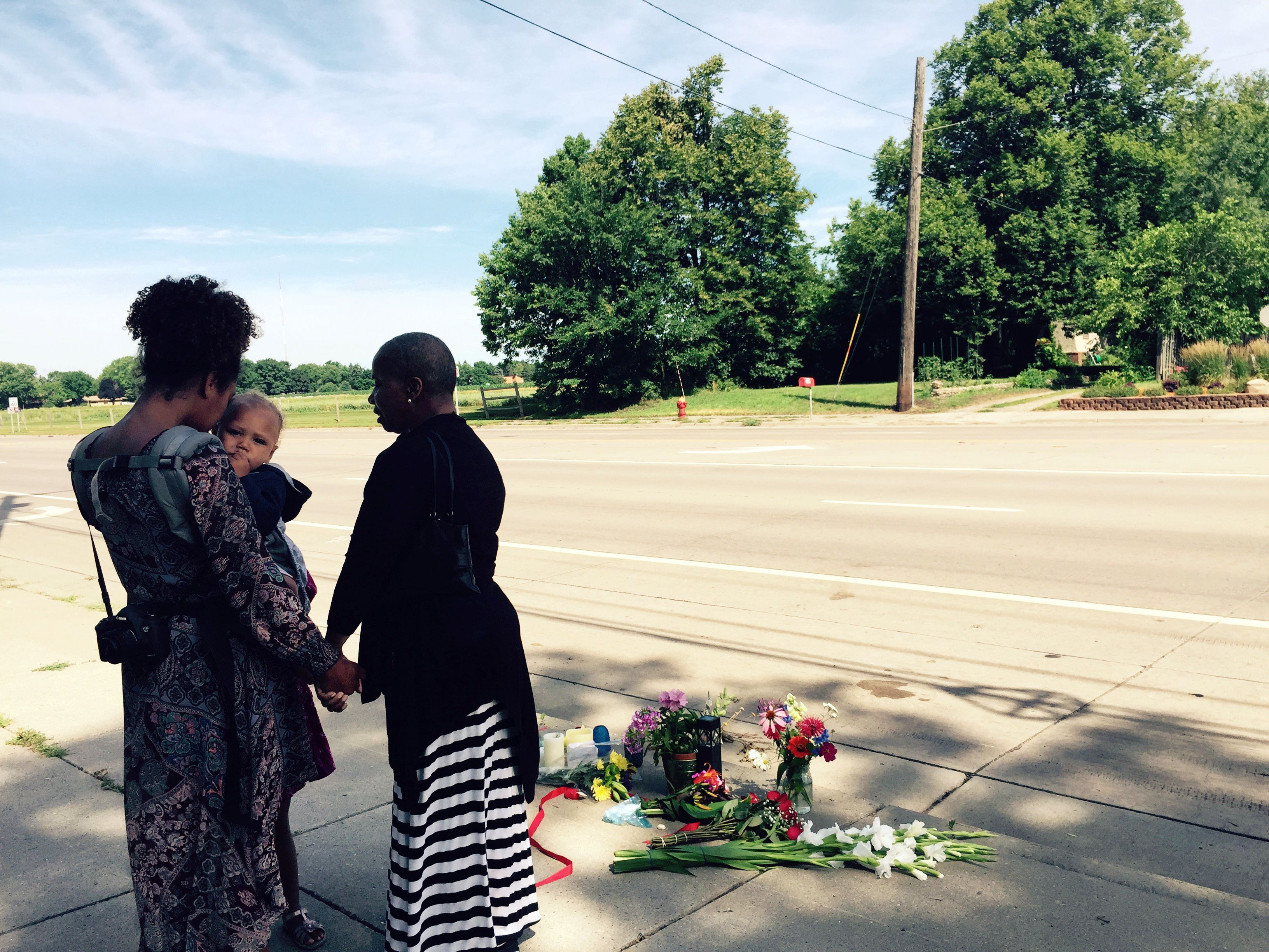 Pastor Patricia Bell, right, of St. Paul, Minnesota, prays on July 7, 2016, with Gabriella Dunn and her children Oakland Dunn, 1, and Chloe Dunn, 4, at the scene of the latest shooting of a black man by police in Falcon Heights, Minnesota. (Getty)