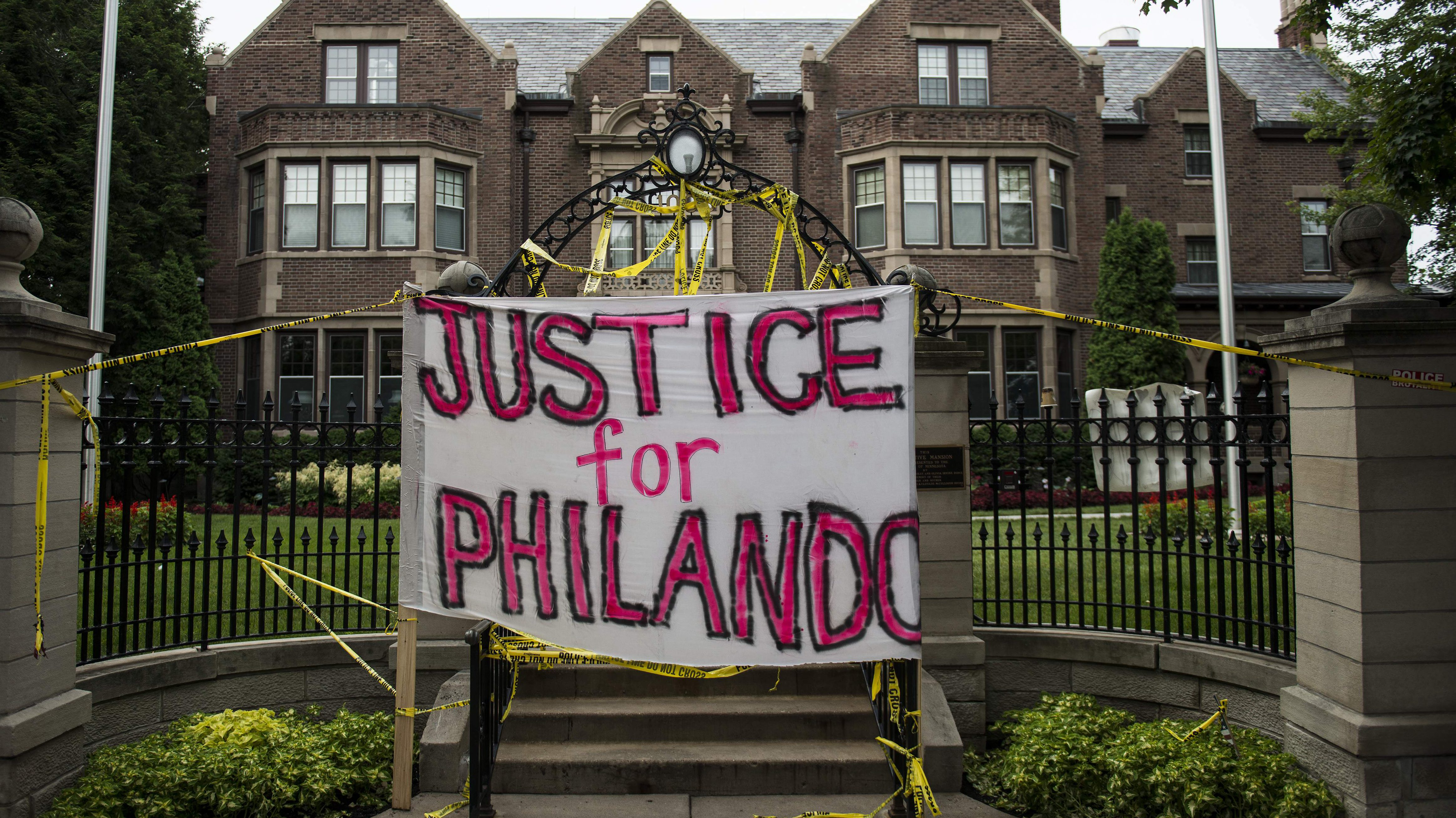 """A sign reading, """"Justice for Philando,"""" and police tape are draped over the entrance of the Governor's Mansion following the police shooting death of a black man on July 7, 2016. (Getty)"""