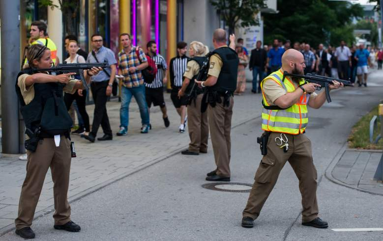 MUNICH, GERMANY - JULY 22: Police officers guard with guns as other officers escort people from inside the shopping center as they respond to a shooting at the Olympia Einkaufzentrum (OEZ) at July 22, 2016 in Munich, Germany. According to reports, several people have been killed and an unknown number injured in a shooting at a shopping centre in the north-western Moosach district in Munich. Police are hunting the attacker or attackers who are thought to be still at large. (Photo by Joerg Koch/Getty Images)