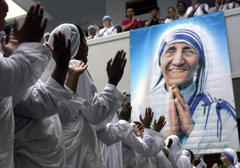 KOLKATA, INDIA:  Indian nuns of Missionaries of Charity gesture as they sing rhymes standing beside a big potrait of the late Mother Teresa while taking part in a prayer to observe her 8th death anniversary, at Mother House in Kolkata, 05 September 2005.  A few hundred nuns with a good number of volunteers took part in the morning prayer to mark the day.    AFP PHOTO/Deshakalyan CHOWDHURY  (Photo credit should read DESHAKALYAN CHOWDHURY/AFP/Getty Images)