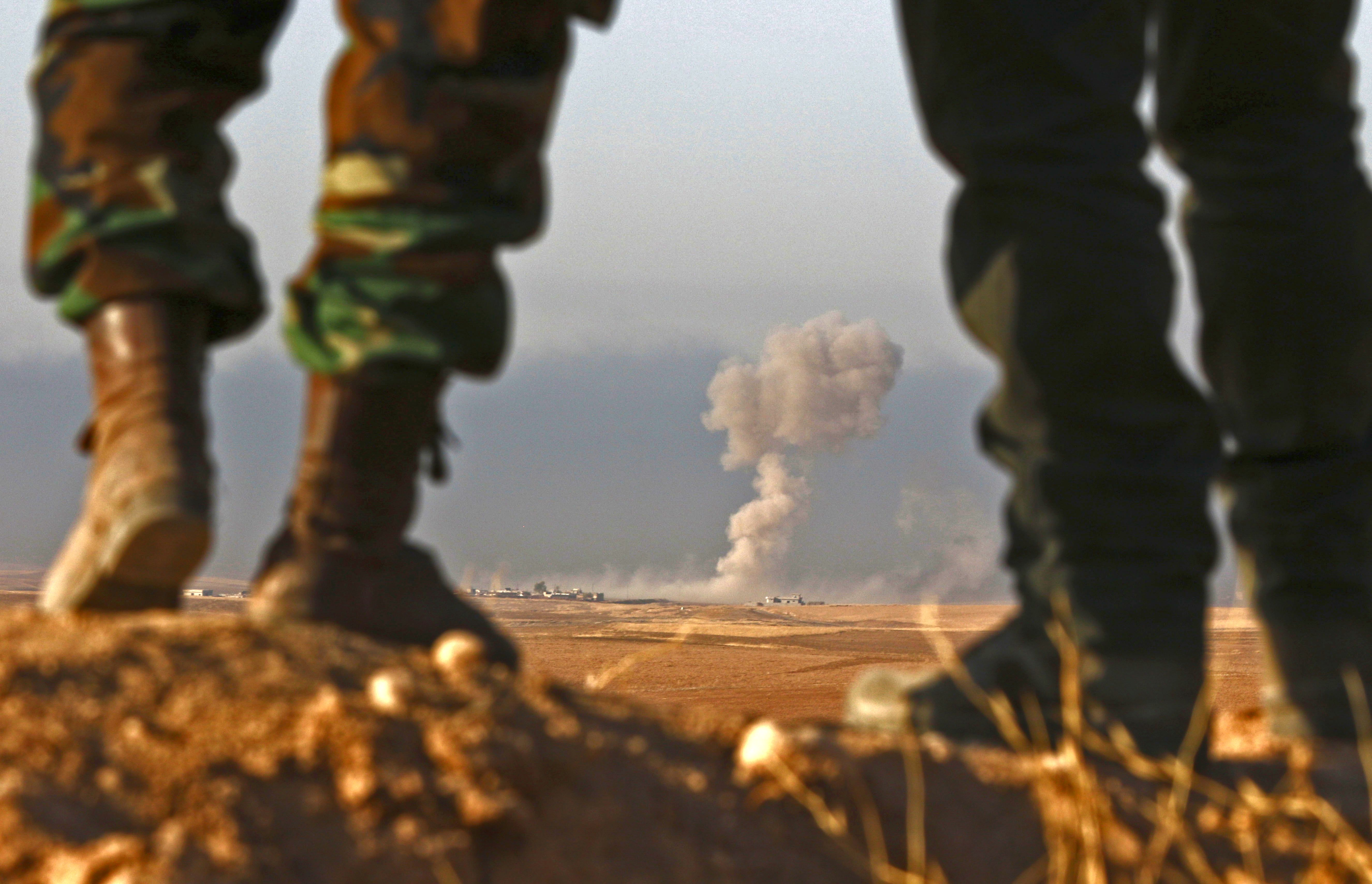 Iraqi Kurdish Peshmerga fighters stand in an area near the town of Bashiqa, some 25 kilometres north east of Mosul, as smoke billows on October 20, 2016, during an operation against Islamic State (IS) group jihadists to retake the main hub city. (Getty)