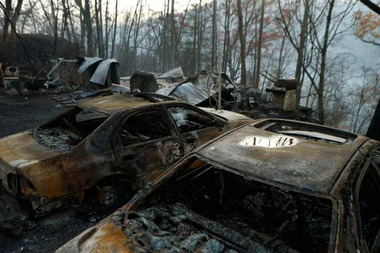 GATLINBURG, TN - NOVEMBER 29: The remains of a home and cars smolder after a wildfire November 29, 2016 in Gatlinburg, Tennessee. Thousands of people have been evacuated from the area and over 100 houses and businesses were damaged or destroyed after drought conditions helped the fire spread through the foothills of the Great Smoky Mountains. (Photo by Brian Blanco/Getty Images)
