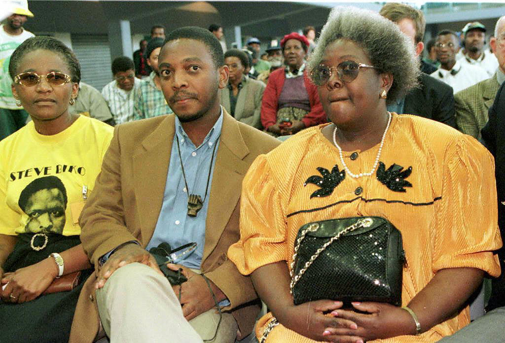 Biko's son, Nkosinathi is flanked by his mother Ntsiki Biko, right,  and an unidentified supporter wearing a T-shirt bearing Biko's portrait. (Getty)