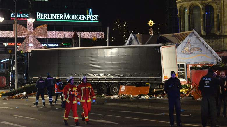 Fireworkers pass by the truck that crashed into a christmas market in Berlin, on December 19, 2016 killing at least one person and injuring at least 50 people. Ambulances and police rushed to the scene after the driver drove up the pavement of the market in a central square popular with tourists less than a week before Christmas, in a scene reminiscent of the deadly truck attack in Nice. / AFP / Odd ANDERSEN (Photo credit should read ODD ANDERSEN/AFP/Getty Images)