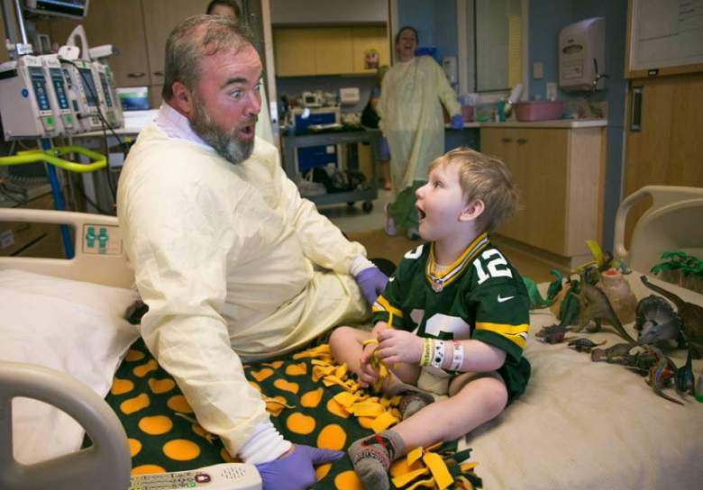 Green Bay Packers coach Mike McCarthy meets with a sick child as part of a charity visit. (Getty)