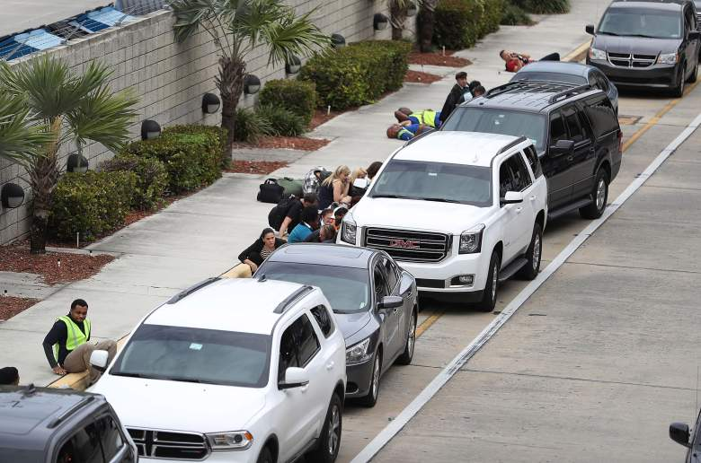 People take cover behind cars outside of Terminal 2 of Fort Lauderdale-Hollywood International airport after a shooting took place near the baggage claim on January 6 in Fort Lauderdale, Florida. (Getty)