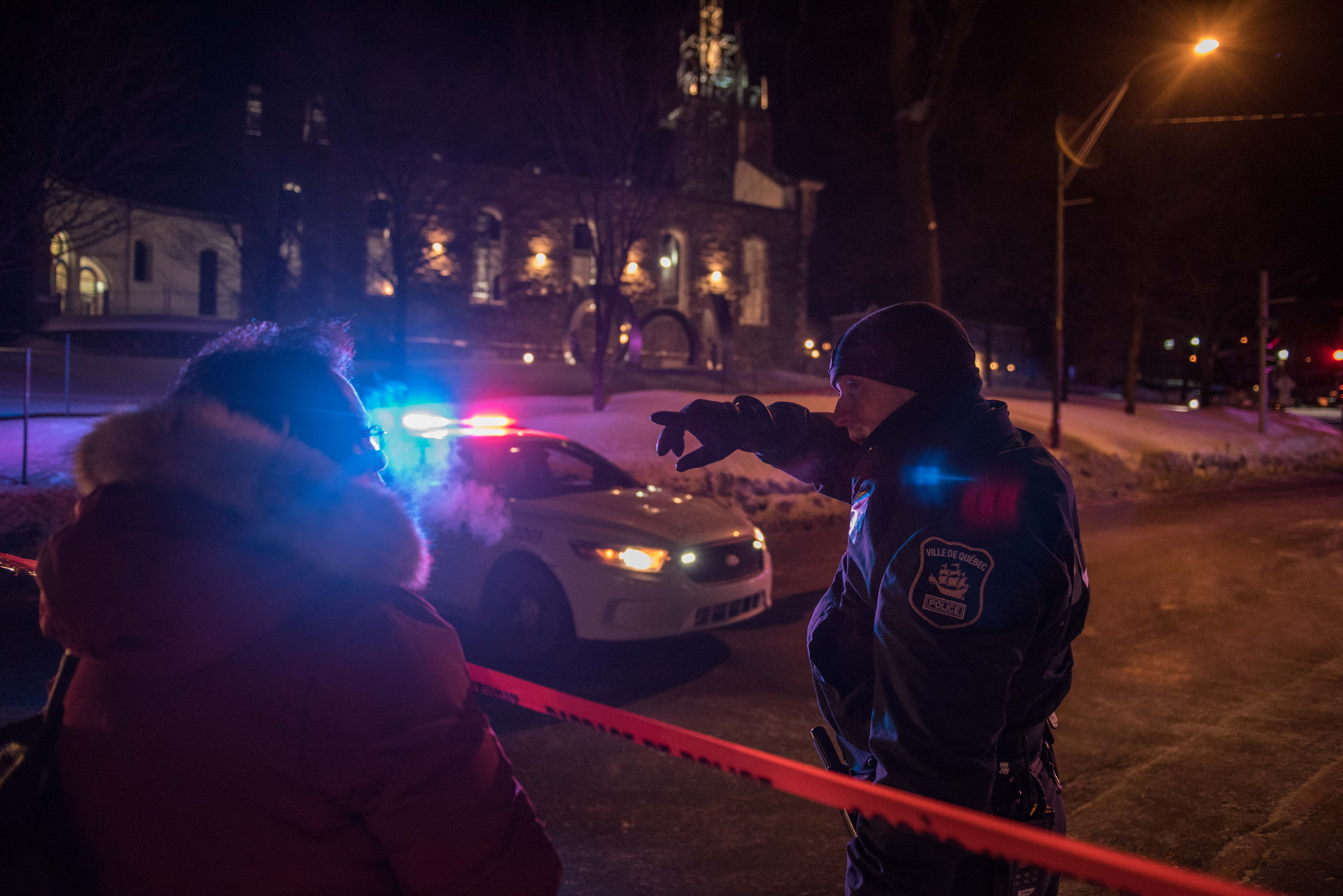 A Canadian police officer talks to a woman after a shooting in a mosque at the Québec City Islamic cultural center on Sainte-Foy Street in Quebec city on January 29, 2017. (Getty)