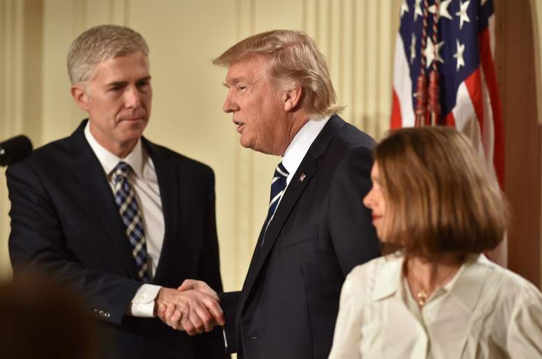 Judge Neil Gorsuch (L) shakes hands with US President Donald Trump after he was nominated for the Supreme Court, as his wife stands nearby. (Getty)