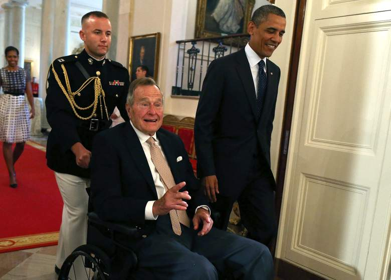 WASHINGTON, DC - JULY 15: Former U.S. President George H. W. Bush sits in a wheelchair as U.S. President Barack Obama (R) escorts him into the East Room during an event at the White House, July 15, 2013 in Washington, DC. Bush joined President Obama in hosting the event to honor the 5,000th Daily Point of Light Award winner. (Photo by Mark Wilson/Getty Images)