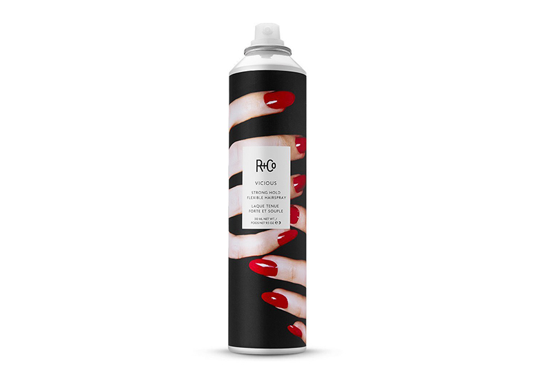 Image of black hair spray bottle with label that looks like it is being gripped by woman