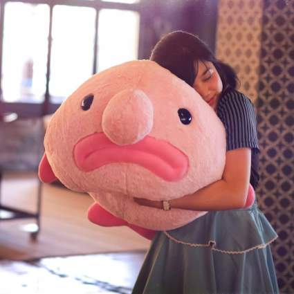 Woman holding giant blobfish plush