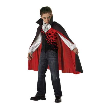 Young boy in black and red vampire cape