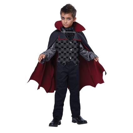 Young boy in gothic vest and vampire cape