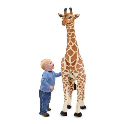 Toddler with giant giraffe plushie