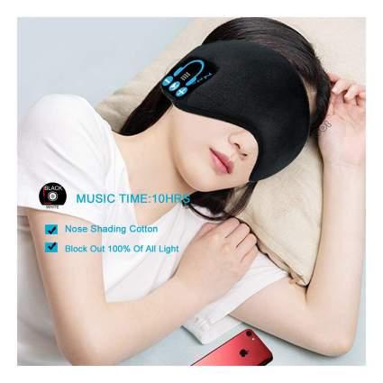 Woman wearing back sleep mask headphones