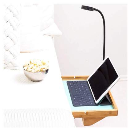 Wooden bed shelf with laptop and lamp