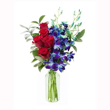 red rose and blue orchid bouquet in glass vase