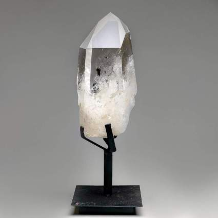 Large clear quartz crystal on black metal stand